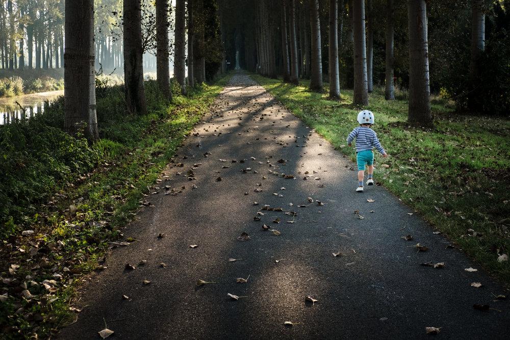 jongen wandelt tussen bomen