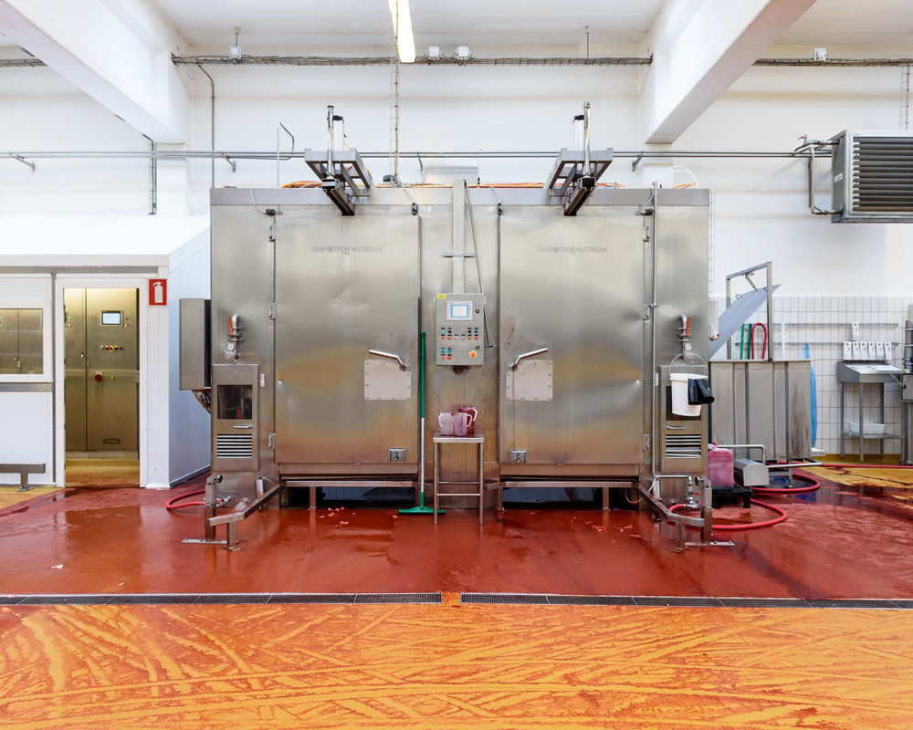 The cabinet in which the red sausages are dyed with carmine. The red liquid on the floor is excess dye.