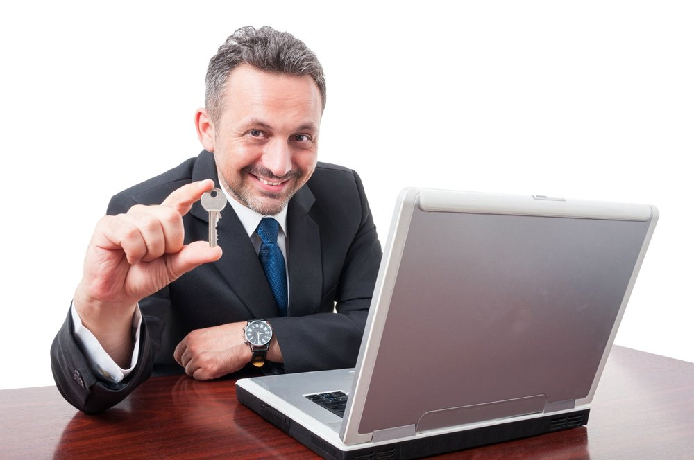 Man holding key while sitting at desk with a laptop