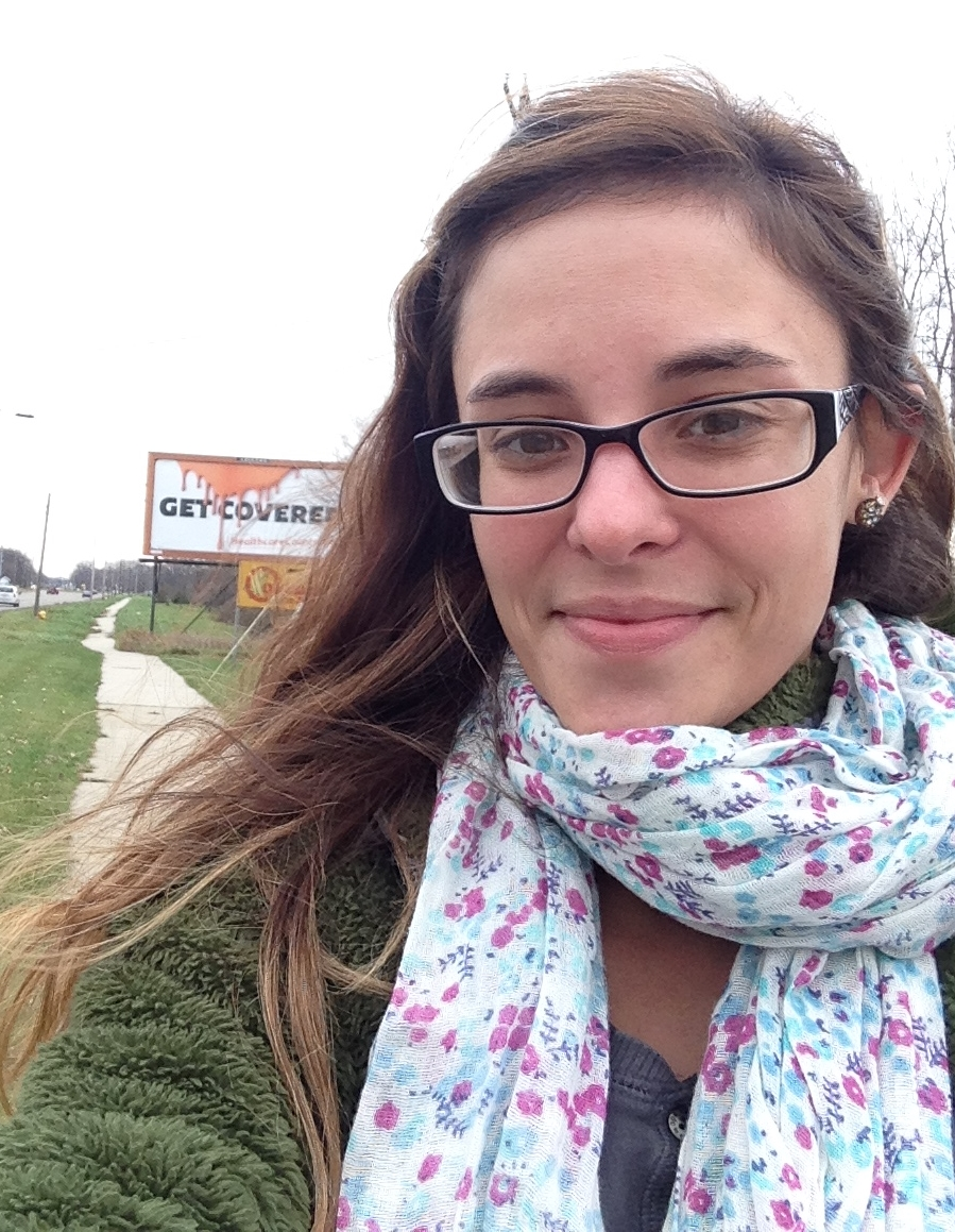 Haley posing with a selfie of herself and the Get Covered billboard in the background.