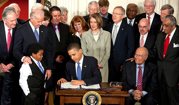 Former Representative Dingell (D-MI) is sitting to the left of President Obama because of his longstanding dedication to universal health coverage legislation.