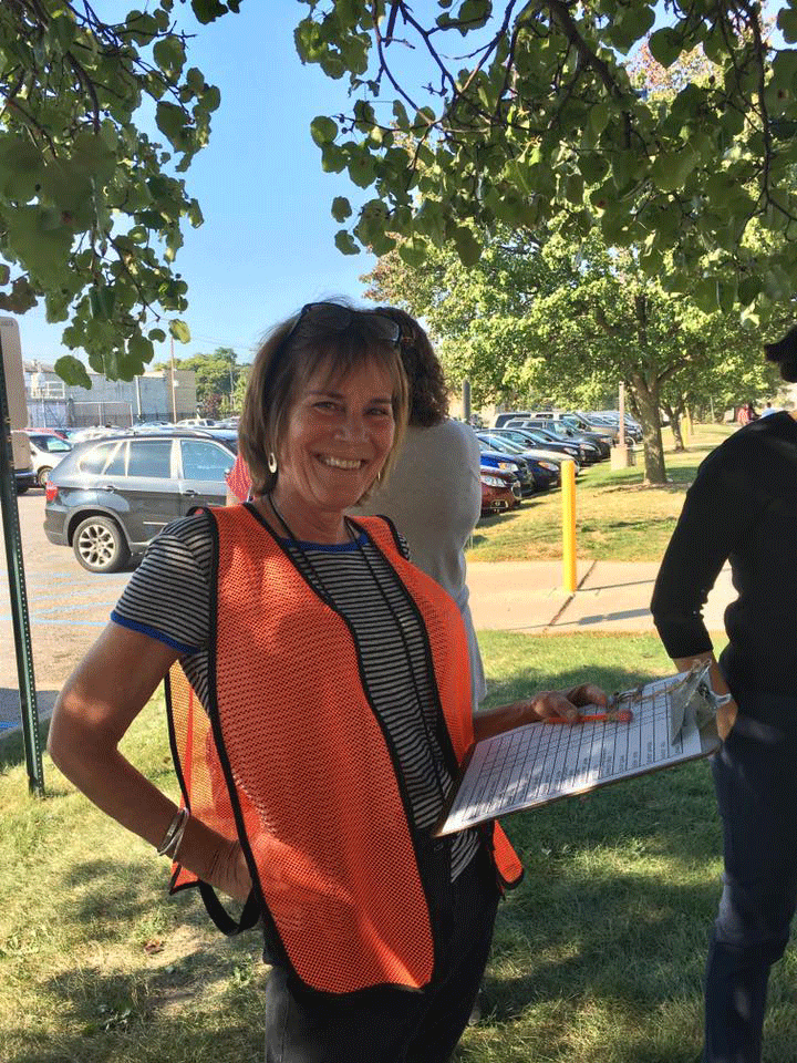 Krista rocks the orange safety vest as she has people check in at a fire safety drill.