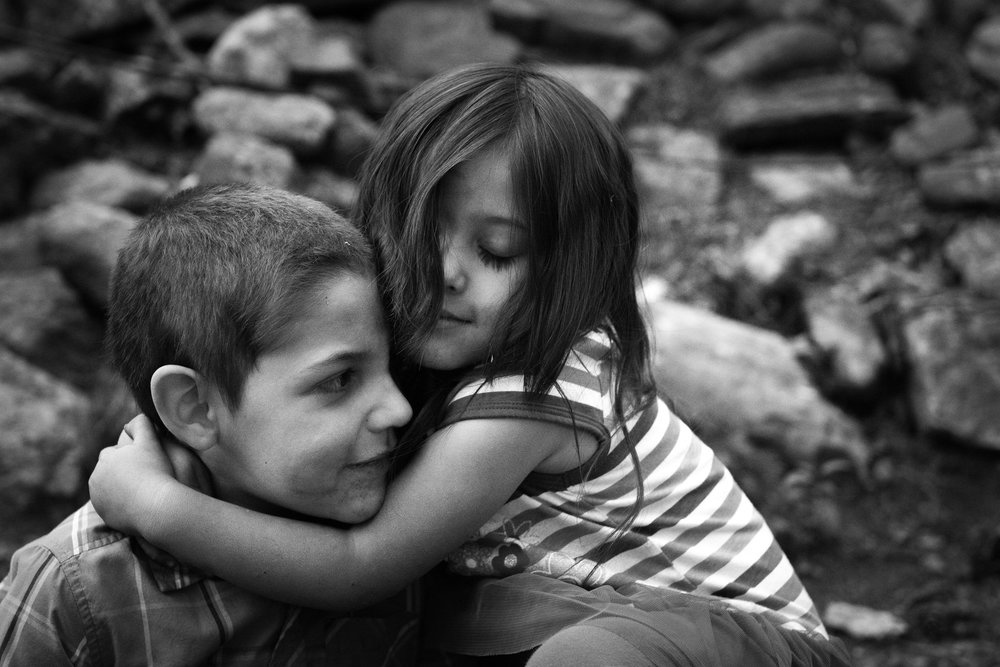 Molly Rees Photo - Black and White Documentary Childhood Photography - Portrait of siblings hugging by M. Menschel