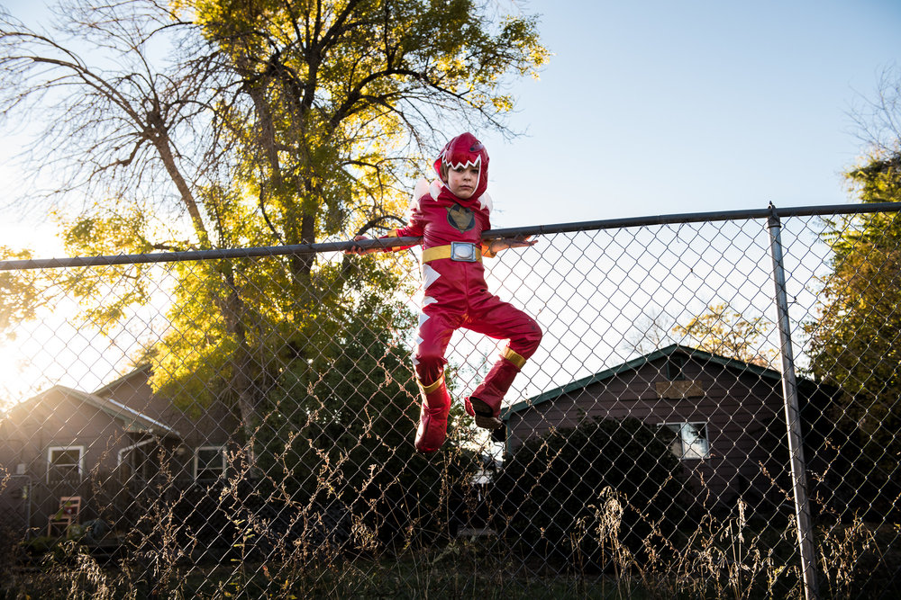 Molly Rees Photo - Documentary Childhood Photography - Portrait of a boy on a fence in a Power Rangers Halloween costume by M. Menschel