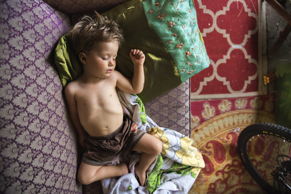 Molly Rees Photo - Documentary Childhood Photography - colorful overhead portrait of young boy sleeping by M. Menschel