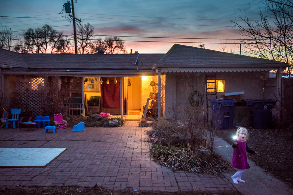 Molly Rees Photo - Documentary Childhood Photography - Portrait of girl with flashlight by house at sunset by M. Menschel