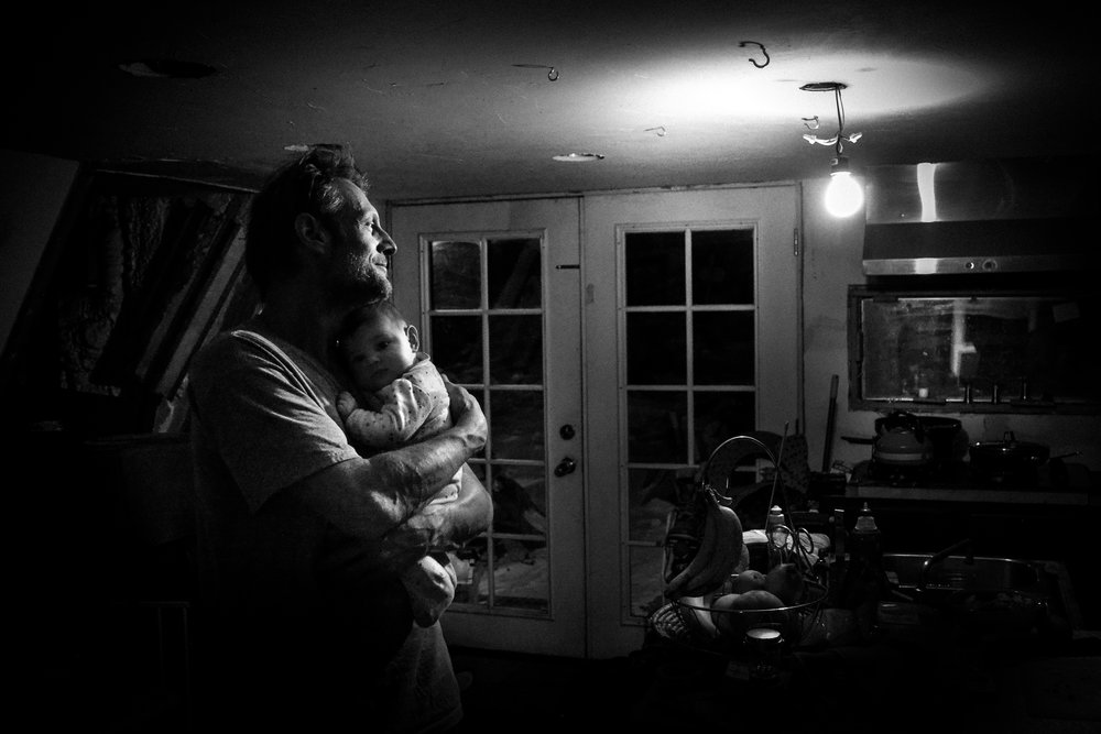 Molly Rees Photo - Black and White Documentary Family Photography - Father and baby portrait in kitchen at night by M. Menschel