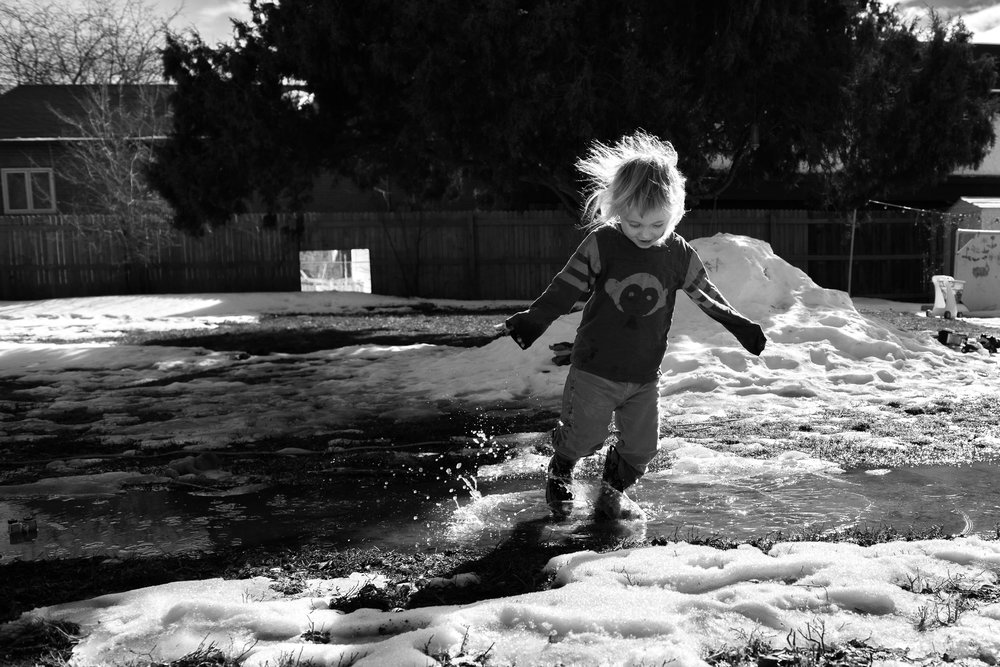 Blog - The Pen & Camera - Gratitude Journal, Inspirational, Friendship, Painting, Home, Motherhood, Writing, Denver, Colorado -  Molly Rees Photo - Black and White Documentary Childhood Photography - girl playing in melting snow in spring by M. Menschel