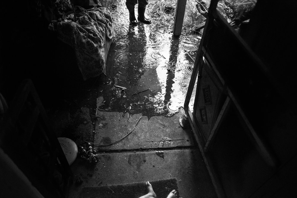 Blog - The Pen & Camera - Inspirational, Spirituality, Denver, Colorado, Writing - Molly Rees Photo - Black and White Documentary Childhood Photography - flooded front porch with boots in rain puddle by M. Menschel