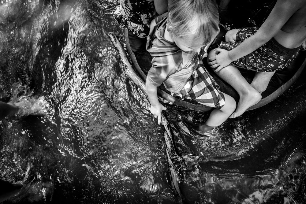 Blog - The Pen & Camera - Molly Rees Photo - Black and White Documentary Childhood Photography - children tubing in stream through woods at Belleview Park in Denver, Colorado by M. Menschel