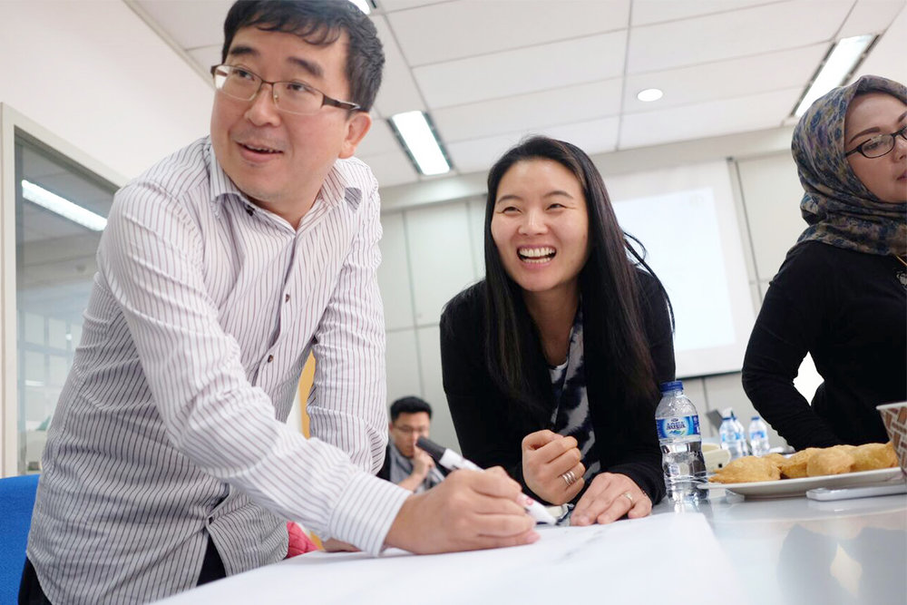 Joo Jun, one of the Program Managers of the Workplace Cooperation Program, working with a committee member.