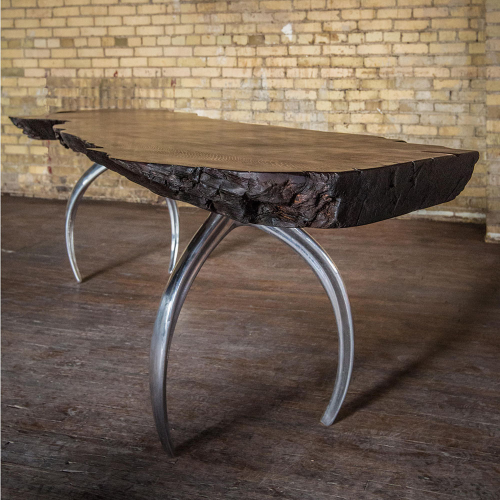 Custom dining table with historic redwood burl surface and cast aluminum wishbone-shaped table legs.