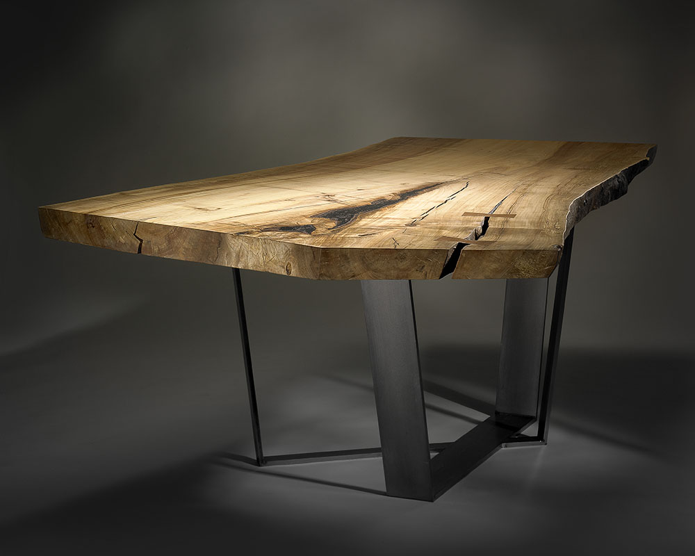 Custom dining table with spalted maple slab and cast metal legs.
