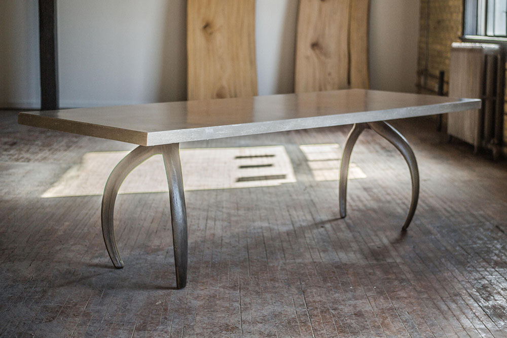 A custom communal dining table; surface is a slab of ECC, legs are cast iron finished with a nordy bronze plate.