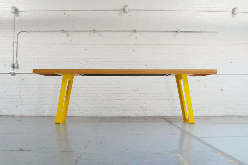 Long communal dining table with yellow steel table legs.