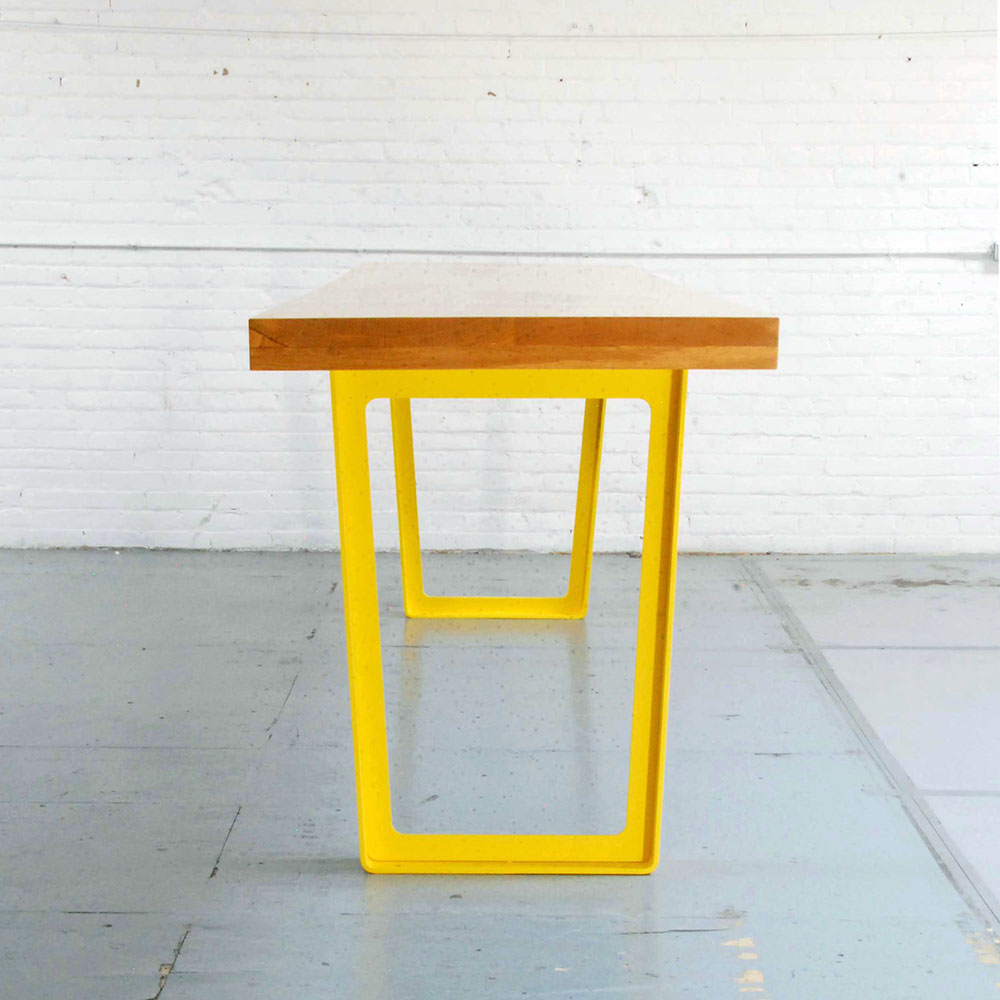 Custom dining table with wood surface and bright yellow legs.