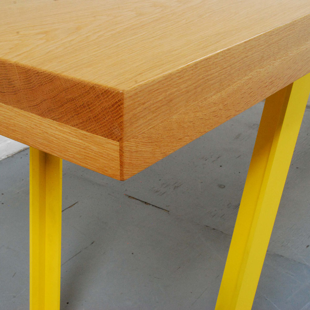Detail showing white oak wood grain and yellow table legs.