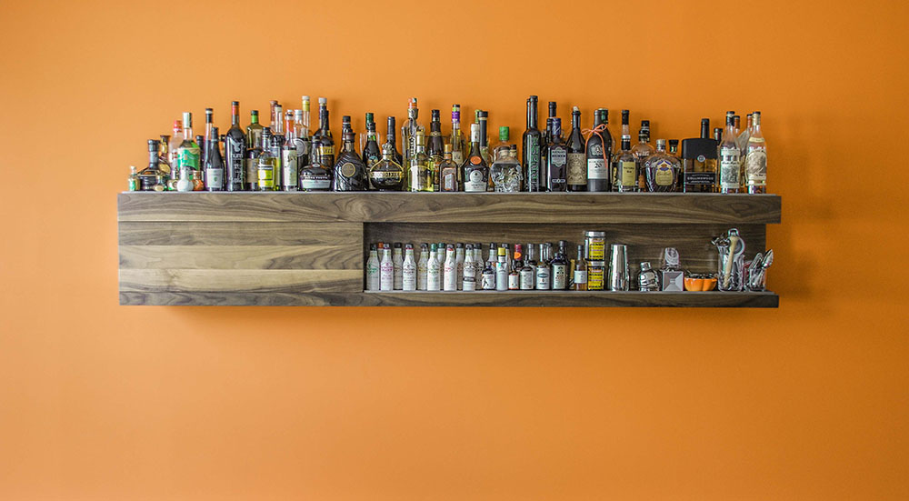 Custom wall-mounted liquor cabinet. Made from solid walnut with a stainless steel border.