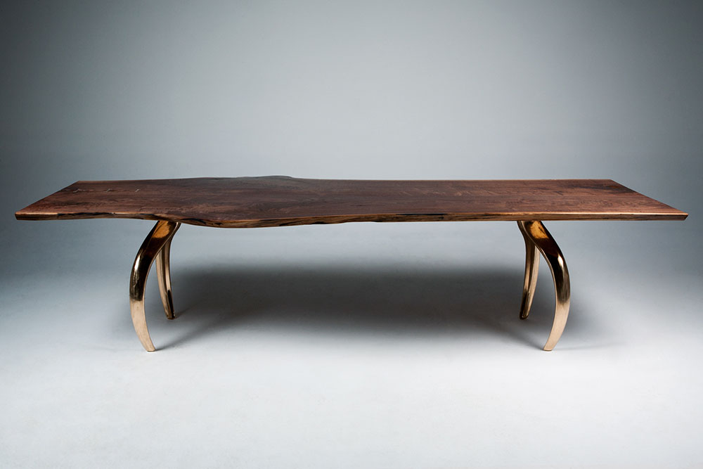 Custom communal dining table: black walnut tabletop with mirror-finish bronze table legs.