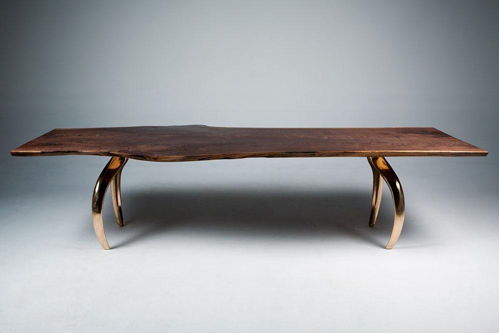 Custom communal dining table: black walnut tabletop with mirror-finish bronze table legs.