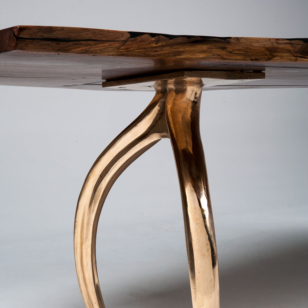 Detail of mirror finish bronze table legs shaped like wishbones.