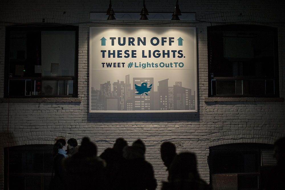 Interactive outdoor advertising in situ; lights are turned out when #LightsOutTO is tweeted.
