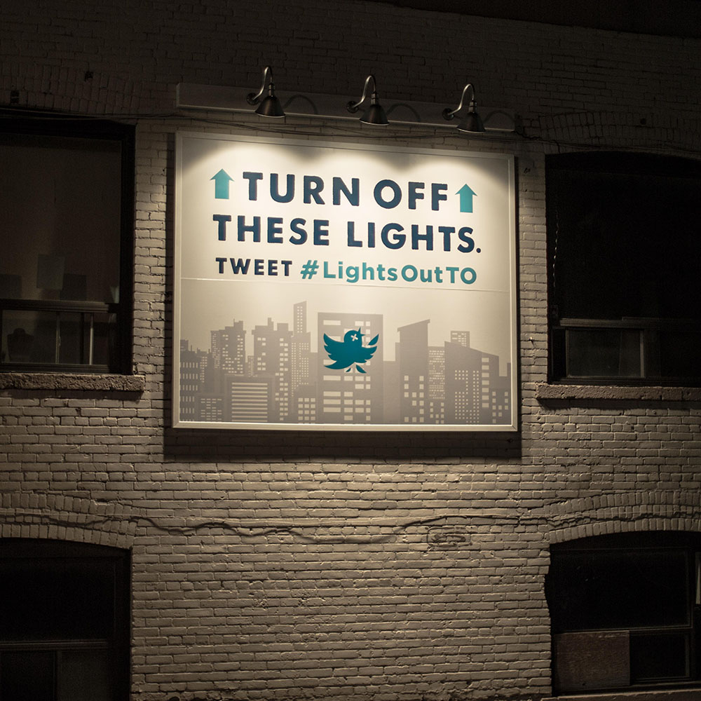 "Interactive outdoor advertising with lights on. Text reads ""TURN OFF THESE LIGHTS. TWEET #LIGHTSOUTTO""."