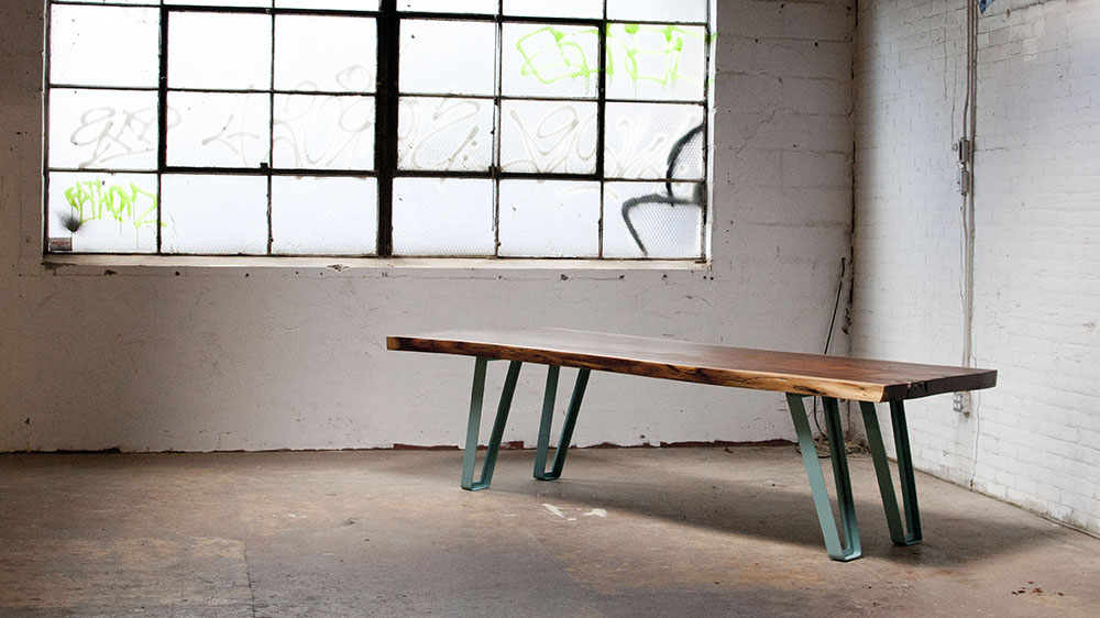 Black walnut slab table with cast metal ribbon legs, in a modern industrial setting.