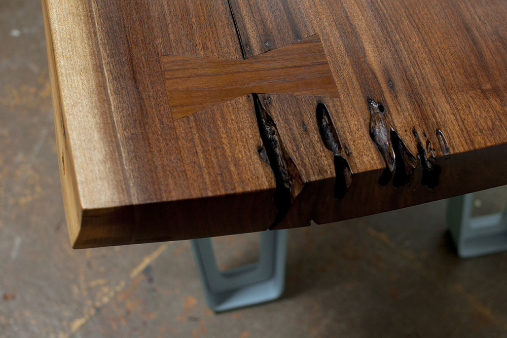 Detail showing wood bow tie in walnut slab tabletop - modern industrial, rustic look.