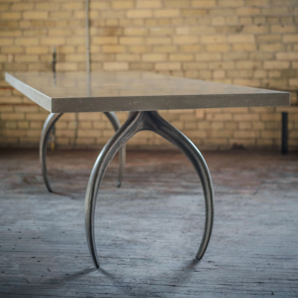 Dining table designed by STACKLAB with wishbone shaped legs.