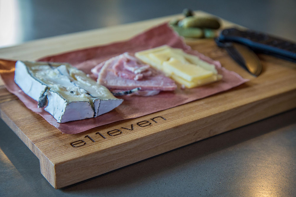 Custom laser-engraved charcuterie board shown with meat and cheese.