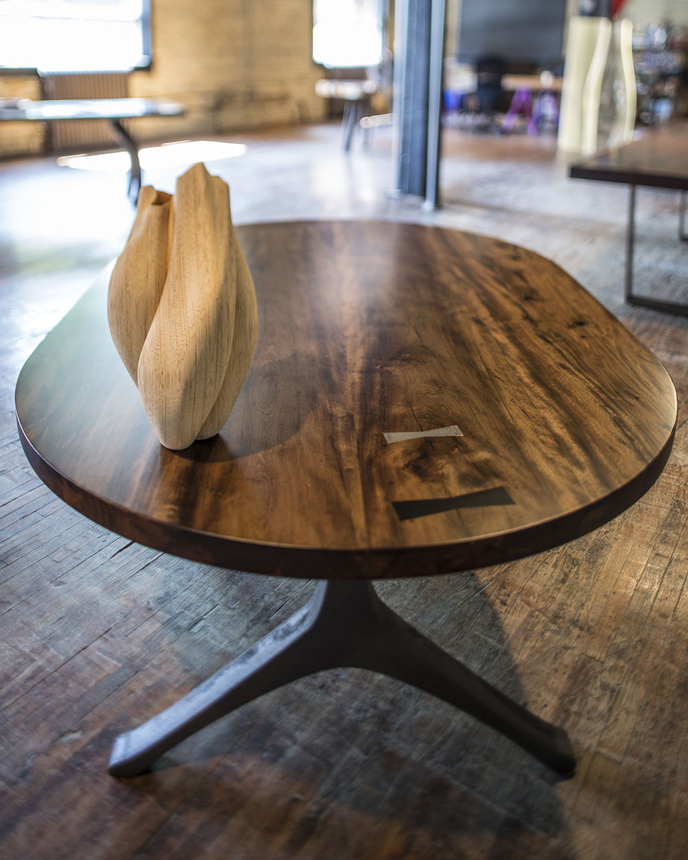 Custom oval wood dining table with metal legs in modern industrial studio space with wooden vase.