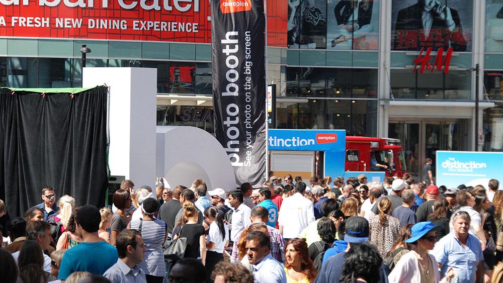 Large crowd surrounding advertising kiosk in downtown Toronto - Aeroplan Distinction campaign.
