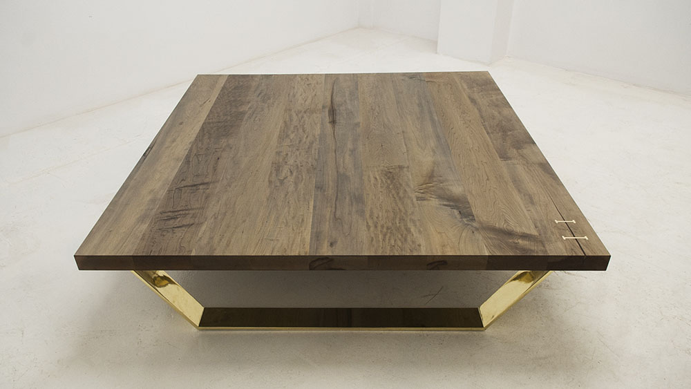 Custom coffee table maple surface wood grain with solid brass stitches and brass legs.
