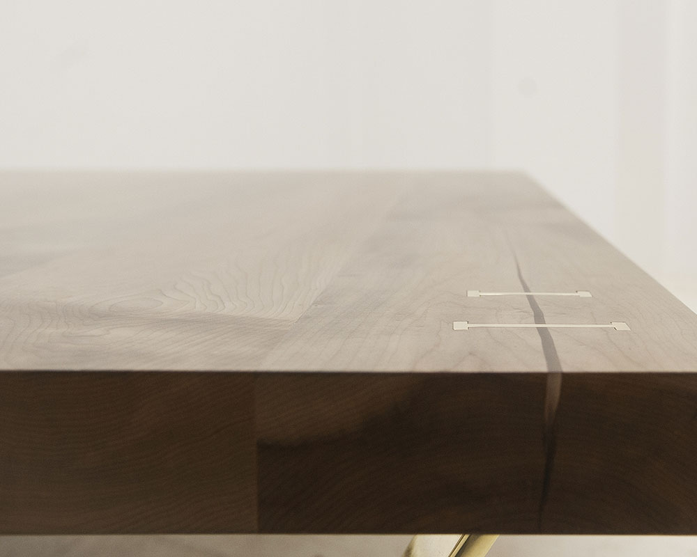 Detail showing brass stitches in oxidized maple coffee table top.