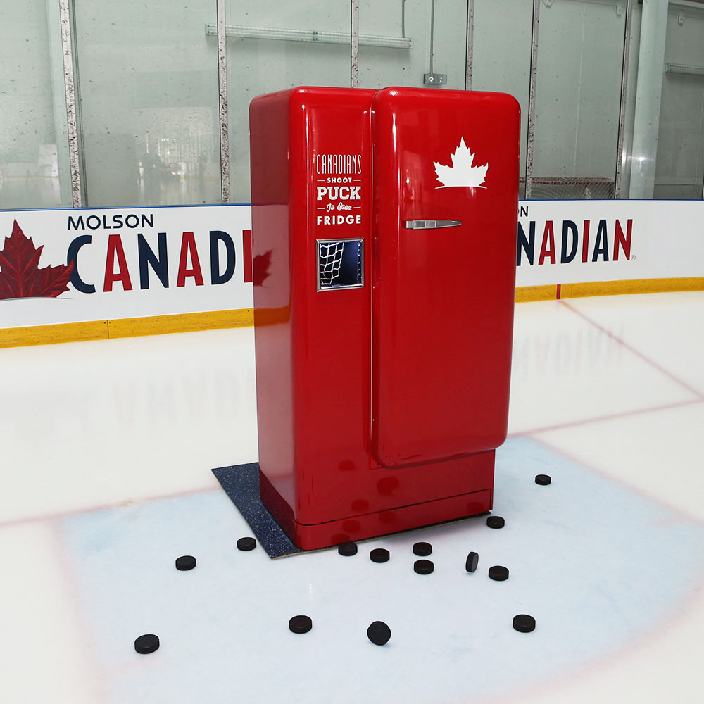Molson Slap Shot Fridge on ice rink surrounded by hockey pucks, with door closed.