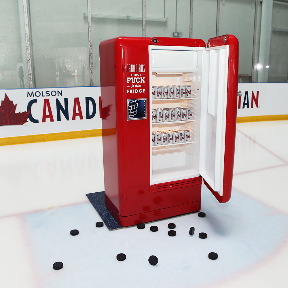 Molson Slap Shot Fridge on hockey rink with door open. Full of beer!
