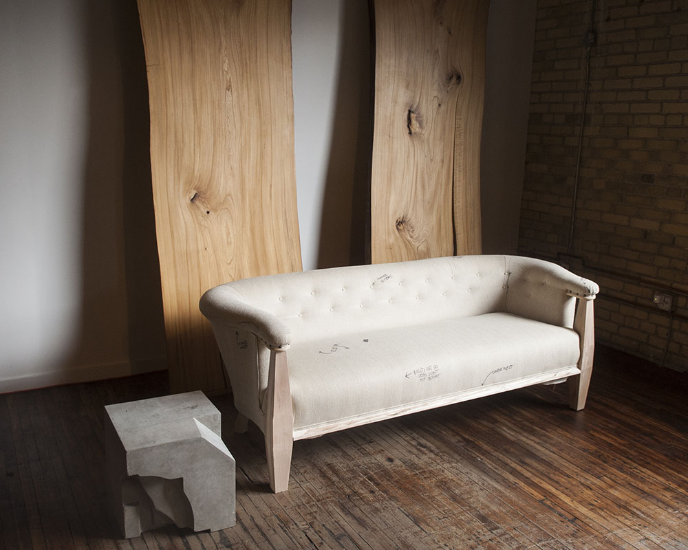 Neutral upholstered sofa in industrial loft studio space with wood and brick.