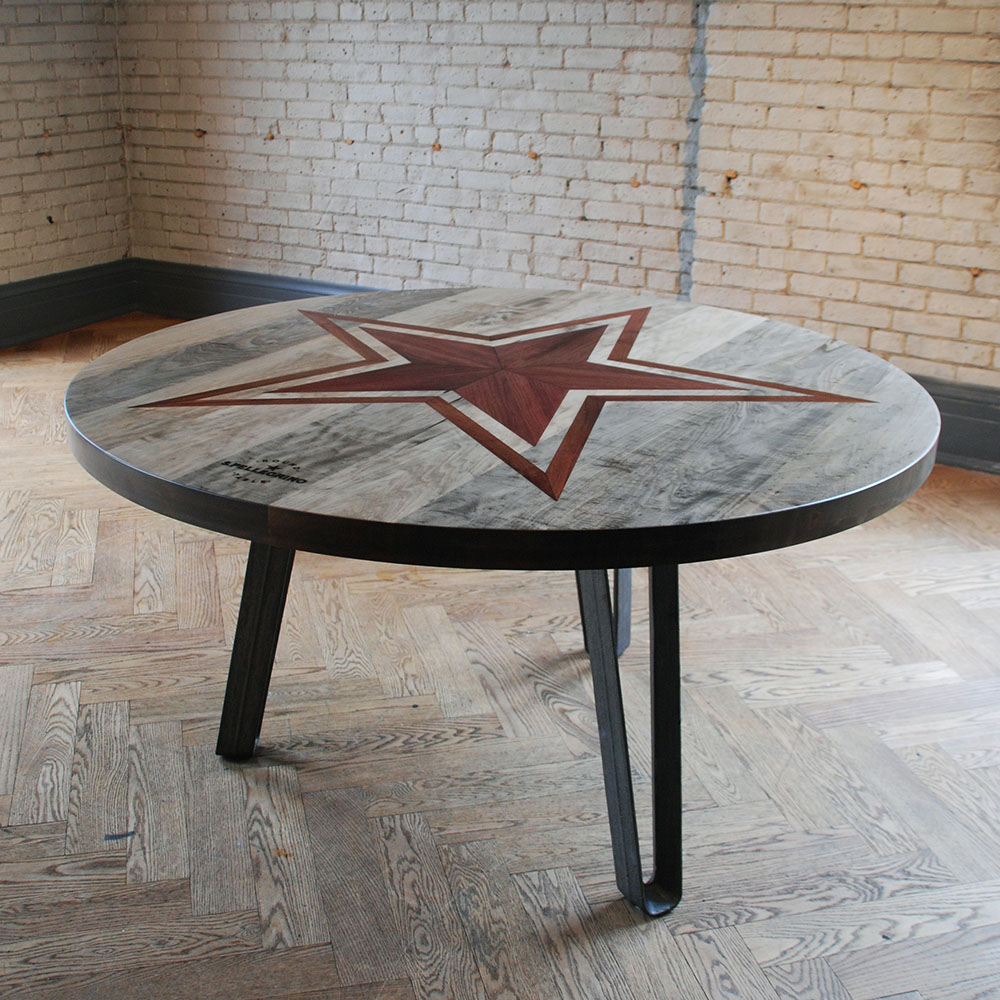 Custom round wood table with star inlay and laser-engraved San Pellegrino logo.