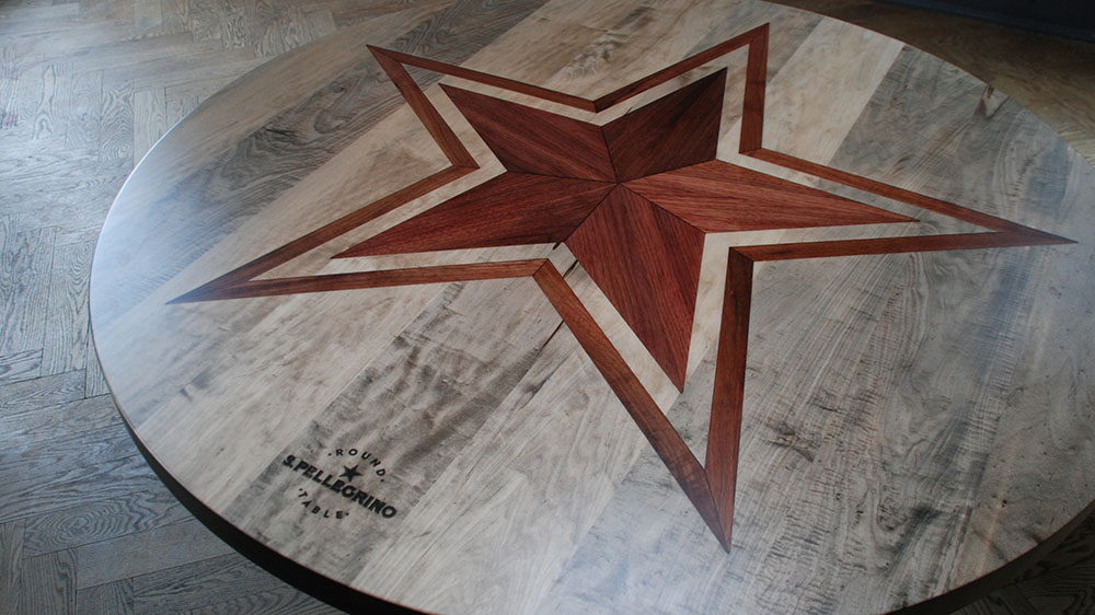 Detail showing customized surface of oxidized maple table top with Canadian black walnut inlay and laser engraved logo.