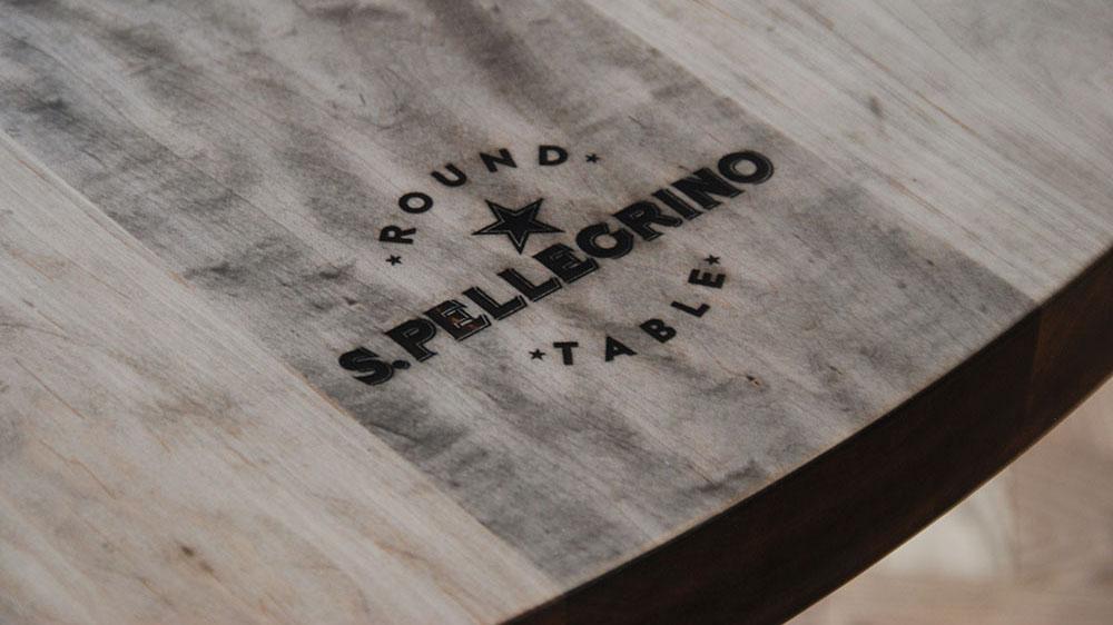 Detail showing fine laser engraving of San Pellegrino logo in wood table top.