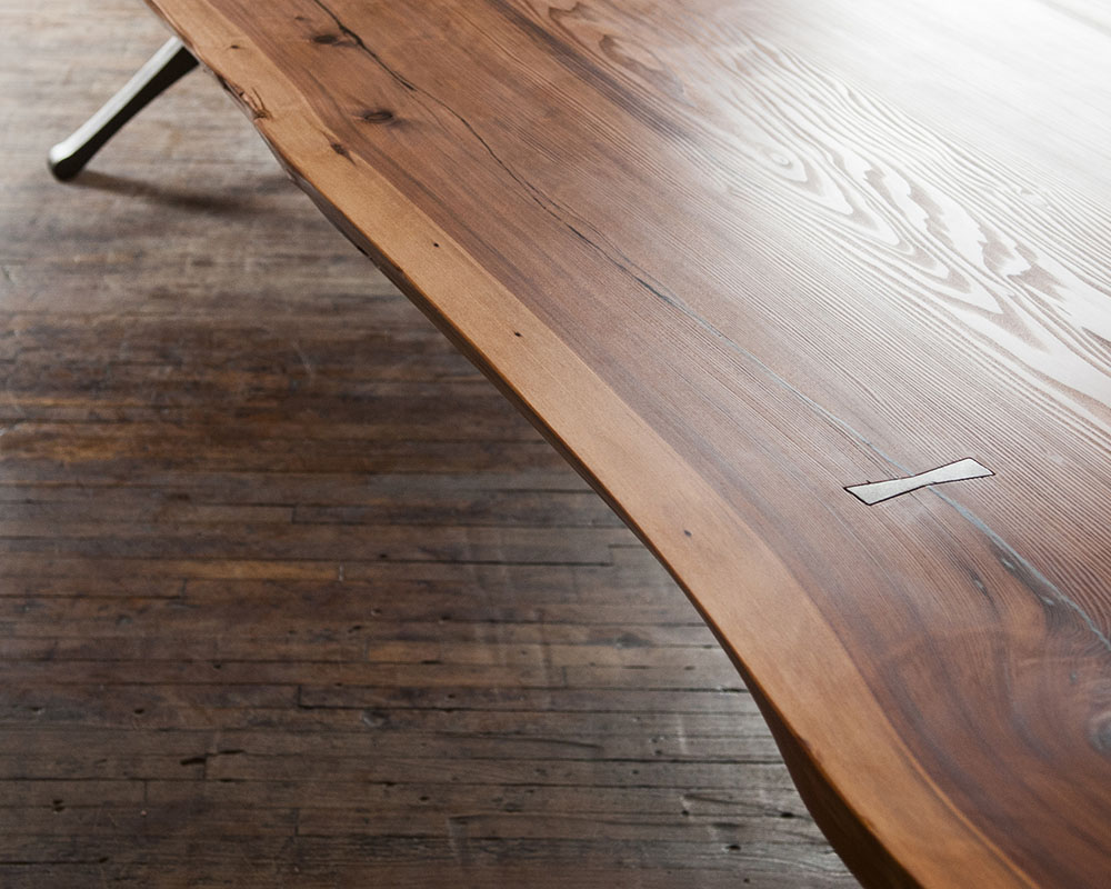 Custom redwood dining table: detail with iron bowties and cast iron table legs.