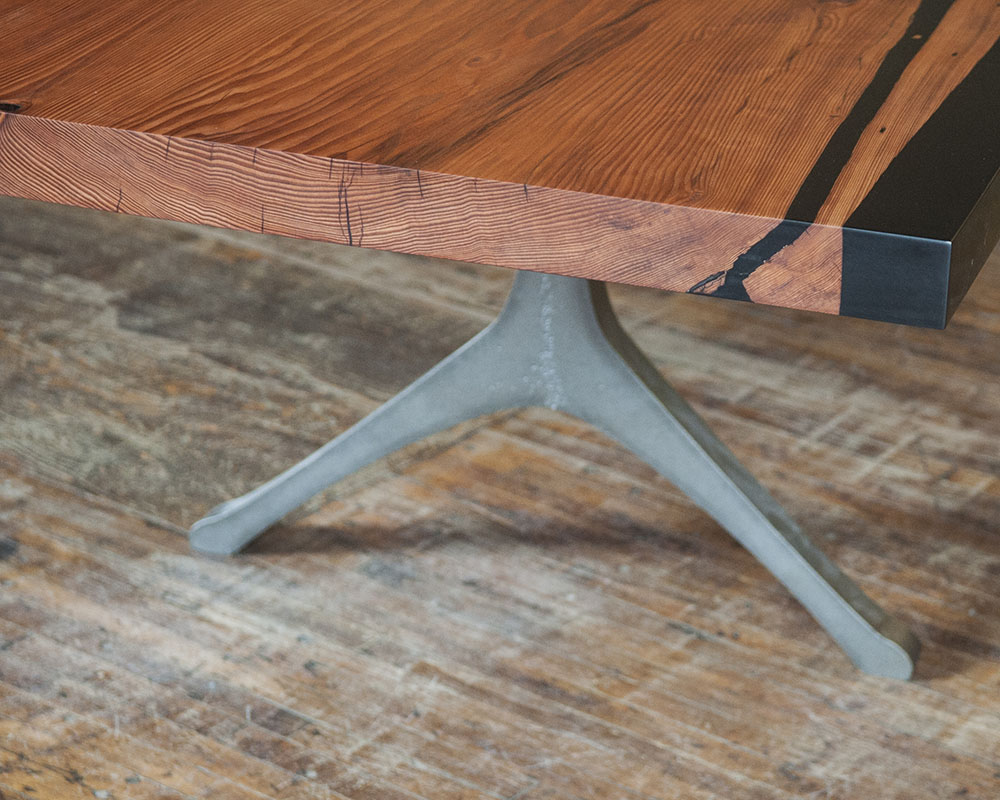Custom wood dining table with black resin edge and cast iron table legs.