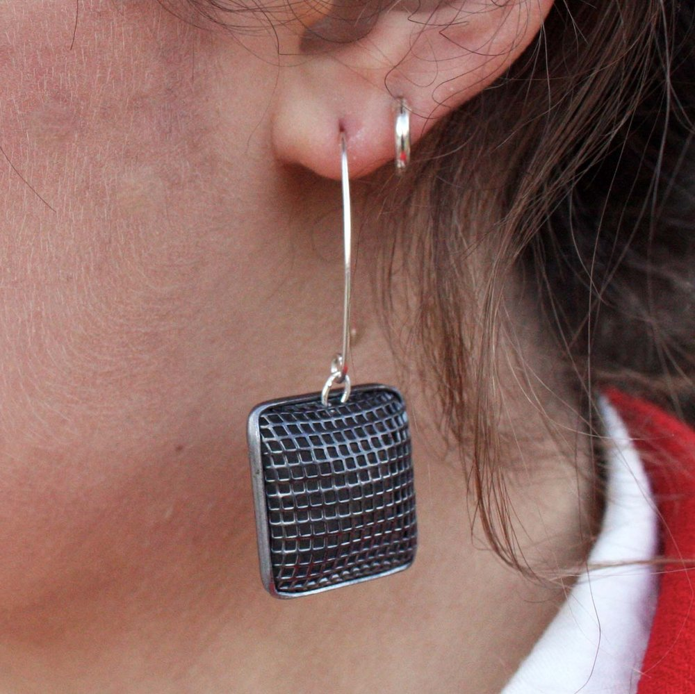 close up of chex silver mesh earring on model
