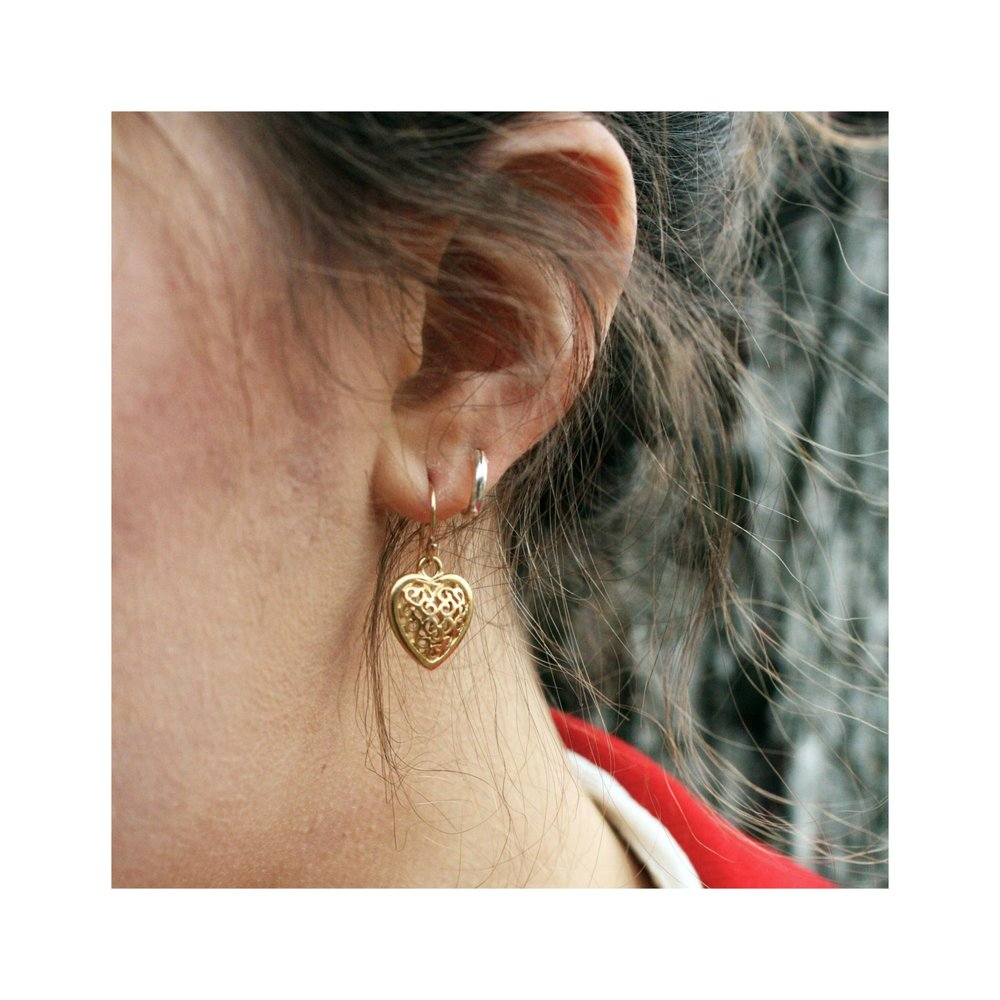 Gold heart earrings on model