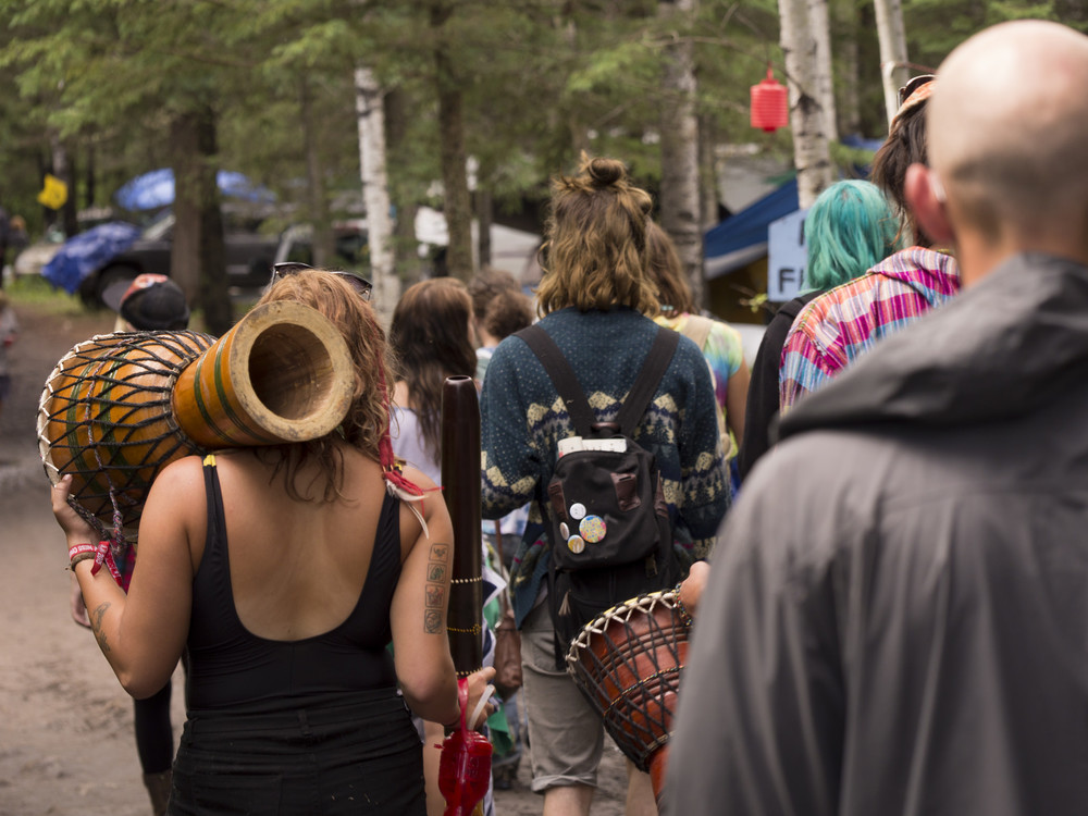 A crowd walks through the mud at the 2015 Ness Creek Music Festival.