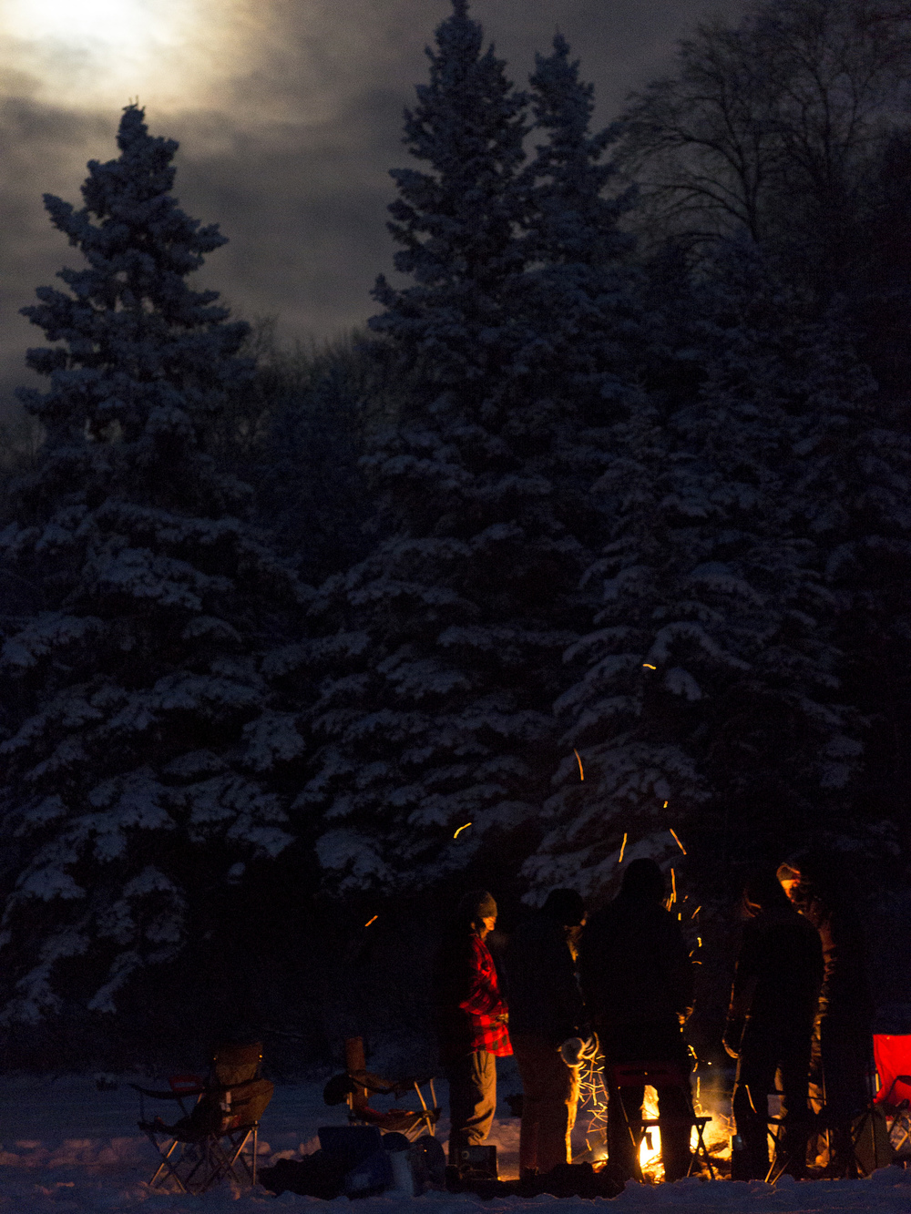 Gathering around with ice and fire under a moon-lit sky.