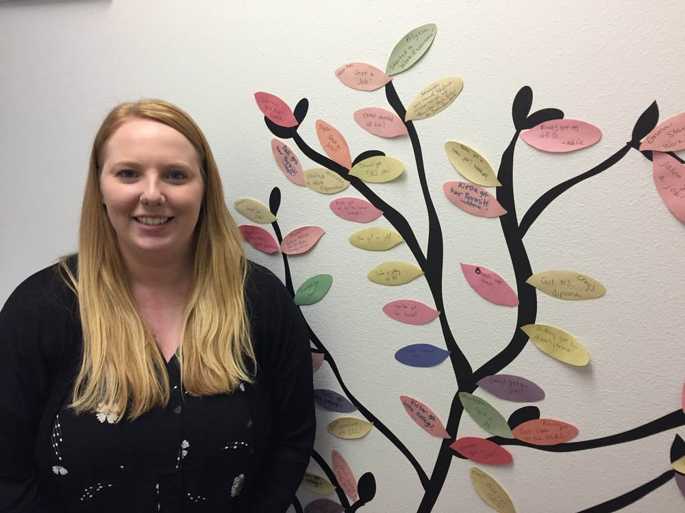 "Brianna Vincent, Services Manager of Riverfront School and Career Center in front of the Job Training ""Success Tree"" to celebrate current and past client achievements."