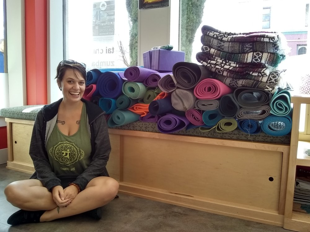 Hannah Stone operations manager at Eugene Yoga with all the donated yoga supplies