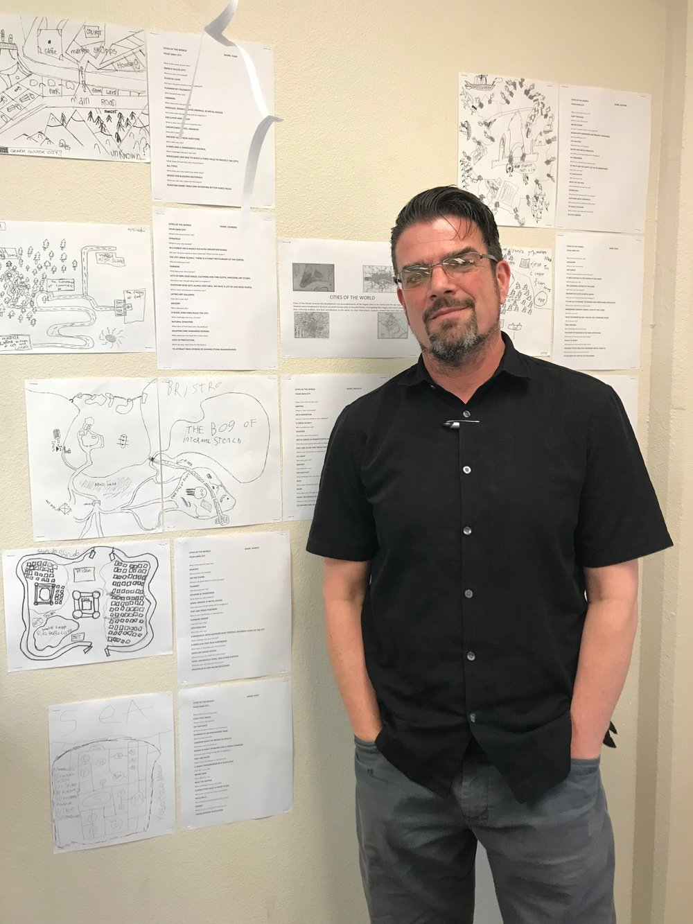 Chris Gordon stands next to a display of student designed cities from his class Cities of the World
